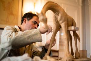Sculpteur Damien Colcombet modelant une girafe en terre